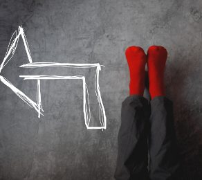 Male legs with red socks leaning on gray wall upside down with drawn direction arrow pointing to left. Youth education youth guidance student guide consultation advisory concept.